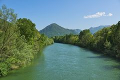 Spring landscape over the river Toce. Spring season on the river Toce with forest on the sides and mountains in the background and clouds in the sky Stock Image