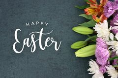 Happy Easter holiday script text over dark background texture and flowers. Spring season still life with Happy Easter holiday script text over dark black Stock Images