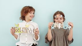 Spring shooting in the studio. Boy and girl holding signs with spring decor. Children laugh, the girl holds a sign