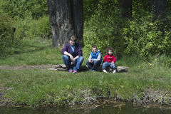 Spring on the shores of mother with children sitting on a log. Royalty Free Stock Images