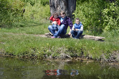 Spring on the shores of mother with children sitting on a log. Stock Images