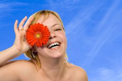 Spring skies and flower fun. Young radiant happy woman having fun under a blue sky stock photography
