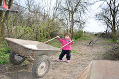 In the spring of small rural girl carries a wheelbarrow. Royalty Free Stock Photos