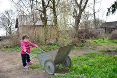 In the spring of small rural girl carries a wheelbarrow. Royalty Free Stock Photo