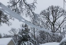 Spring snow covering electric wires attatched to house Royalty Free Stock Photography