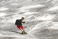 Spring snow surfing 3. Snowboarder in shorts on a bumpy slope during late spring on a heavy colored snow royalty free stock photo