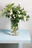 Spring snowflake Leucojum vernum bouquet in glass vase on blue wood table and gray background. Royalty Free Stock Photos
