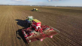 Spring sowing campaign - two tractors pull seeders, a rural landscape. 4K aerial video stock footage