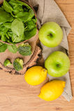 Spring spinach leaves in the bowl, broccoli, lemons and apples Stock Images
