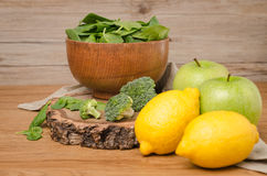 Spring spinach leaves in the bowl, broccoli, lemons and apples Stock Photo