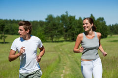 Spring - Sportive couple jogging outdoors. Summer - Sportive couple jogging outdoors in meadow, shallow DOF Royalty Free Stock Images