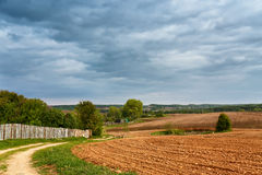 Spring storm clouds above country road. Village and arable land field in spring Royalty Free Stock Photo