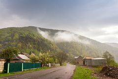 Spring stormy rainy weather. Road and village in green mountain Stock Image