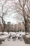 On the spring street of the city are bicycles. The snow hasn`t melted on the lawns yet. Russia, Tyumen stock photography