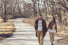 Spring stroll through a forest. Couple holding hands and walking down the road through a forest, enjoying a sunny spring day. Focus on the boyfriend royalty free stock image