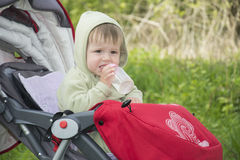 Spring in the stroller little boy sits and drinks water from a b Stock Images