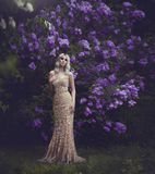 Spring style. Beautiful sensual girl blonde in spring. Blossoming spring garden. Young girl in a gold elegant dress. Young woman in the garden with blooming stock photography