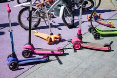 Spring and summer activities - many kick scooters and bicycles in park at children`s playground.  royalty free stock photography