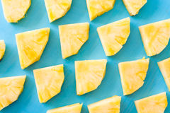 Spring or summer concept : Close up patter of many pieces of yellow pineapple laying on blue wooden table background. Close up patter of many pieces of yellow Stock Image