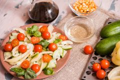 Spring summer diet salad with strawberries, cucumber, green field salad and yogurt mint sauce served in blue plate with cloth. Napkin over grey texture stock photos