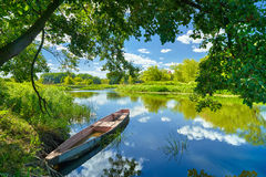 Spring summer landscape blue sky clouds river boat green trees stock images