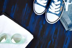 Spring or summer outfit. Flat lay of female sneakers shoes, glasses, T-shirt, top, shorts on a blue background. Copy space. Top view. Spring or summer outfit Royalty Free Stock Photography