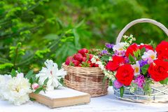Spring summer still life with a bouquet of flowers in a basket, berries ripe strawberries, an old book and white peonies on the ta. Ble on a natural green stock photos