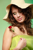 Spring or summer. Young woman girl in hat holding red rose flower. Spring or summer concept. Portrait of curly girl young woman in hat and green dress holding Royalty Free Stock Photos
