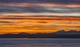 Spring Sunset on the Puget Sound with Olympic Mountains. The Olympic Mountains are Bathed in a Sea of Orange and Red in this Sunset Image from Seattle Royalty Free Stock Photo