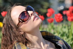 Spring sunbathing. Young woman looks at sun in sun glasses, blurred tulips on background Stock Images