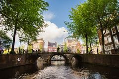 Tour to Europe. Big European city. Spring sunny Amsterdam. The bright clear blue sky with white clouds. Boat trip on the canals of Amsterdam. The bridge over the stock image