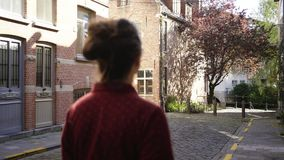 Girl walking between brick wall. Spring sunny day in european city. Following from behind young woman walking between brick walls. Buildings in traditional dutch stock footage