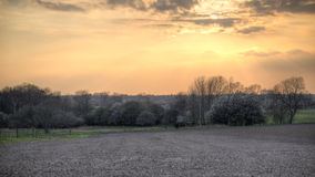 Sunset over ploughed field Royalty Free Stock Photos