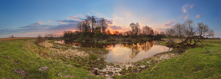 Spring sunset panorama. Small river in evening Royalty Free Stock Photo