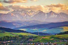 Spring sunset in Tatra Mountains, Pieniny range. Snow caped mountains and green fields and meadows in Malopolska region, Poland. Spring sunset in Tatra Mountains royalty free stock photos