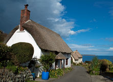 Cottages at Church Cove Cornwall. Spring sunshine and blue skies over the thatched cottages at Church Cove on the Lizard in south west Cornwall Stock Images