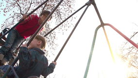 Spring Swing. Two children ride on a swing. Sun - backlight. Slow Motion at a rate of 480 fps stock video