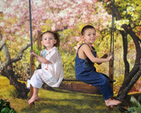 Spring Swinging Preschoolers. Adorable preschoolers sitting on an antique, 2-person swing in a bright spring yard Royalty Free Stock Photography