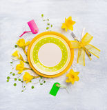Spring table decoration with with narcissus , hyacinths , sign, ribbons , knife and fork on green plate Stock Image