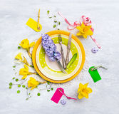 Spring table decoration with with narcissus , hyacinths , sign, ribbons , knife and fork on green plate Royalty Free Stock Photo