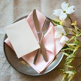 Spring Table Place Setting with dogwood flowers, light pink napkin, silverware and a vertical blank card for menu or invitation. It`s an above view with royalty free stock photo