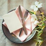 Spring Table Place Setting with dogwood flowers, pink napkin, silverware and a blank card for menu or invitation.