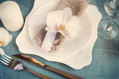 Spring table setting with orchid decorations, candles, wineglass Stock Photo