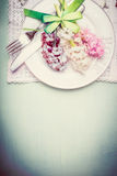 Spring table setting with plate, cutlery, ribbon and pretty hyacinths flowers , top view, border, pastel Stock Photos