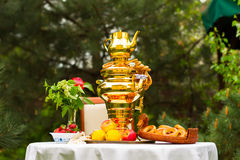 Spring tea party in the garden, on a table covered with a white. Tablecloth, Russian samovar and tea, strawberries on the plate Gzhel, lemons, flowers, drying Royalty Free Stock Image