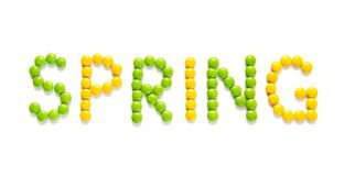Text Spring of candy on isolated white background. Spring. The text Spring made of green and yellow sweet candy dragees on isolated white background. Creative Stock Photography
