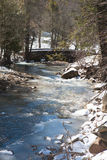 Spring Thaw: Frozen Creek and Bridge Stock Image