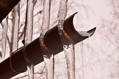 Spring thaw. Icicles froze over the drain. State of water. Parallel royalty free stock photography