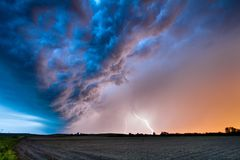 A Spring Thunderstorm at Sunset. Lightning from a spring thunderstorm strikes the ground as the sun sets creating a beautiful scene royalty free stock photo