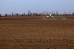 Spring tillage of arable land. Tractor does harrowing and cultivation of arable land preparing it  for sowing Stock Image